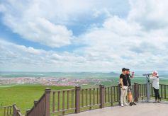 游客在玛曲县外香寺观景台观看玛曲县城全貌