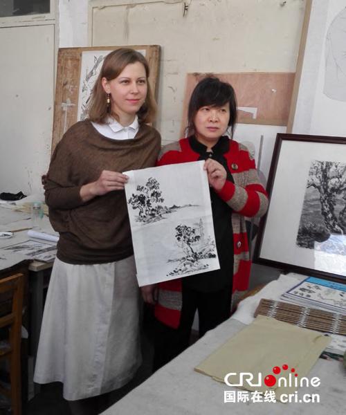 冉妮娅展示现场创作的山水画。摄影:黄蓉