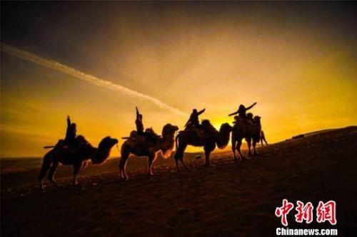 初春时节,游客在鸣沙山观赏敦煌大漠日出。 王斌银 摄
