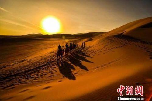 图为初春时节,游客在鸣沙山观赏敦煌大漠日出。 王斌银 摄