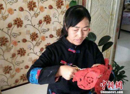 甘肃山丹县民间手艺人周玉梅历时5年时间,用506幅剪纸作品创作出剪纸版《红楼梦》。 钟欣 摄