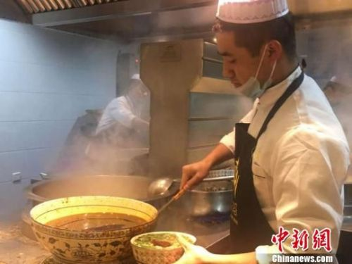 清晨,兰州磨沟沿牛肉面馆的马林将刚出锅的面舀上牛肉汤,放配料,这是他最拿手的活儿。每天卖出去数千碗牛肉面,都是他舀汤端给客人的。 张婧 摄