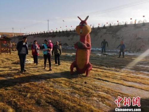 """虽至寒冬,""""稻草人""""吸引游客们络绎不绝前来游玩。 崔琳 摄"""