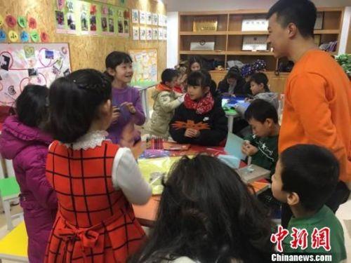 图为胡景蓉正在与老师交流自己制作面具的心得。 张婧 摄