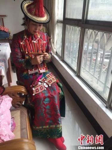 资料图:甘肃裕固族文化传承人瑙尔姬斯在家中绣制裕固族服饰。 杨娜 摄