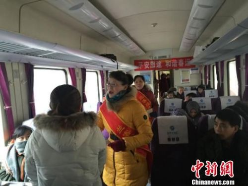 图为志愿者为旅客发放新年画册。 杨娜 摄