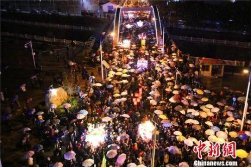 """3月6日,正月十九,天空下起小雨,数万民众撑起雨伞和""""婆婆""""的圣辇一起行进。 全当周 摄"""