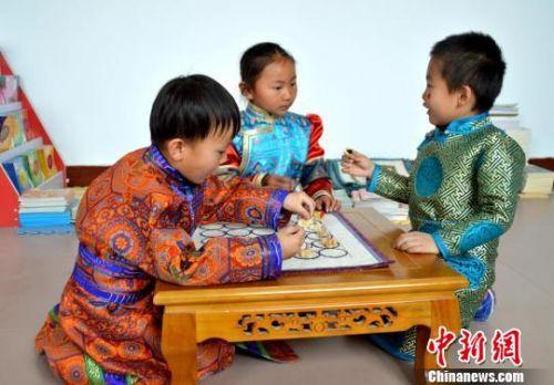 在游戏中,幼儿利用沙嘎的四个面,以四个或五个为一幅,组织各种不同的游戏活动,通过这个活动,可以促进孩子们手、眼、脑协调发展,开发智力。 杨帆 摄