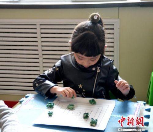 图为幼儿练习沙嘎的玩法。 杨帆 摄