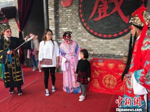 图为王宏荣一家三代人正在戏台上表演崇信弦子腔。 艾庆龙 摄