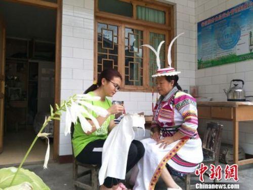 图为志愿者与甘肃陇南文县白马藏族妇女一起制作特色文化产品。 李铭垣 摄