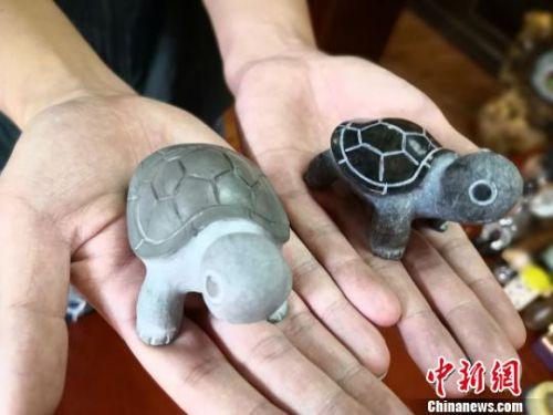 """刘宗学的儿子用石头研发创制的新作品""""茶宠""""。 丁思 摄"""