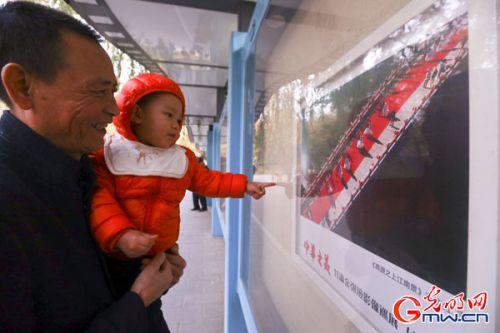 市民在展出窗前驻足观看展览