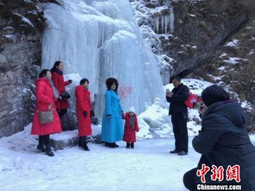 图为游客在冰瀑前拍照留念。 闫姣 摄
