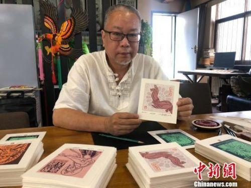 图为徐晋林展示藏书票。 徐雪 摄
